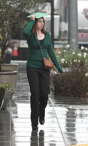 Carly Narlesky uses a folder to protect herself from the rain in Sacramento, Calif, Monday, Oct. 22, 2012.  The first storm of the season swept through Northern California bringing rain to the lower elevations and snow in the mountains. Photo: Rich Pedroncelli, Associated Press