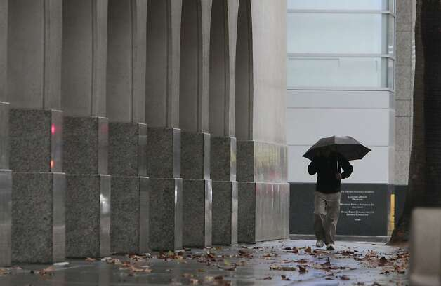 A man huddles under an umbrella as rain blankets Sacramento, Calif, Monday, Oct. 22, 2012.  The storm swept through Northern California bringing rain to the lower elevations and snow in the mountains. Photo: Rich Pedroncelli, Associated Press