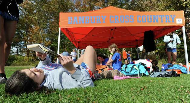 Danbury High School runner Tara Strosser, a junior, reads Mary Shelley's Frankenstein prior to the FCIAC girls high school cross country championship at Waveny Park in New Canaan, Thursday afternoon, Oct. 18, 2012. Photo: Bob Luckey / Greenwich Time