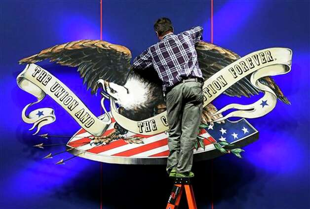 A worker adjusts the backdrop on stage in preparation for Monday's presidential debate between President Barack Obama and Republican presidential candidate, former Massachusetts Gov. Mitt Romney, Sunday, Oct. 21, 2012, at Lynn University in Boca Raton, Fla. (AP Photo/Charlie Neibergall) Photo: Charlie Neibergall, ASSOCIATED PRESS / AP2012