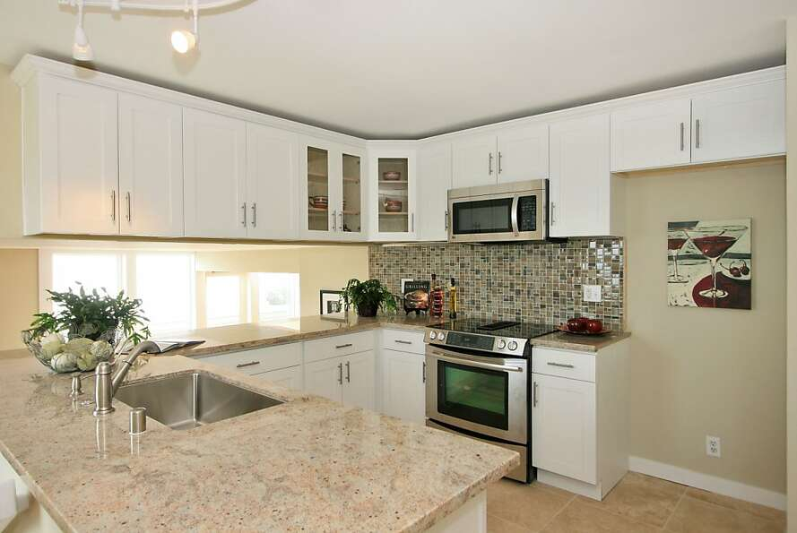 The kitchen is newly renovated and features a glass tile backsplash and an eat-in area.