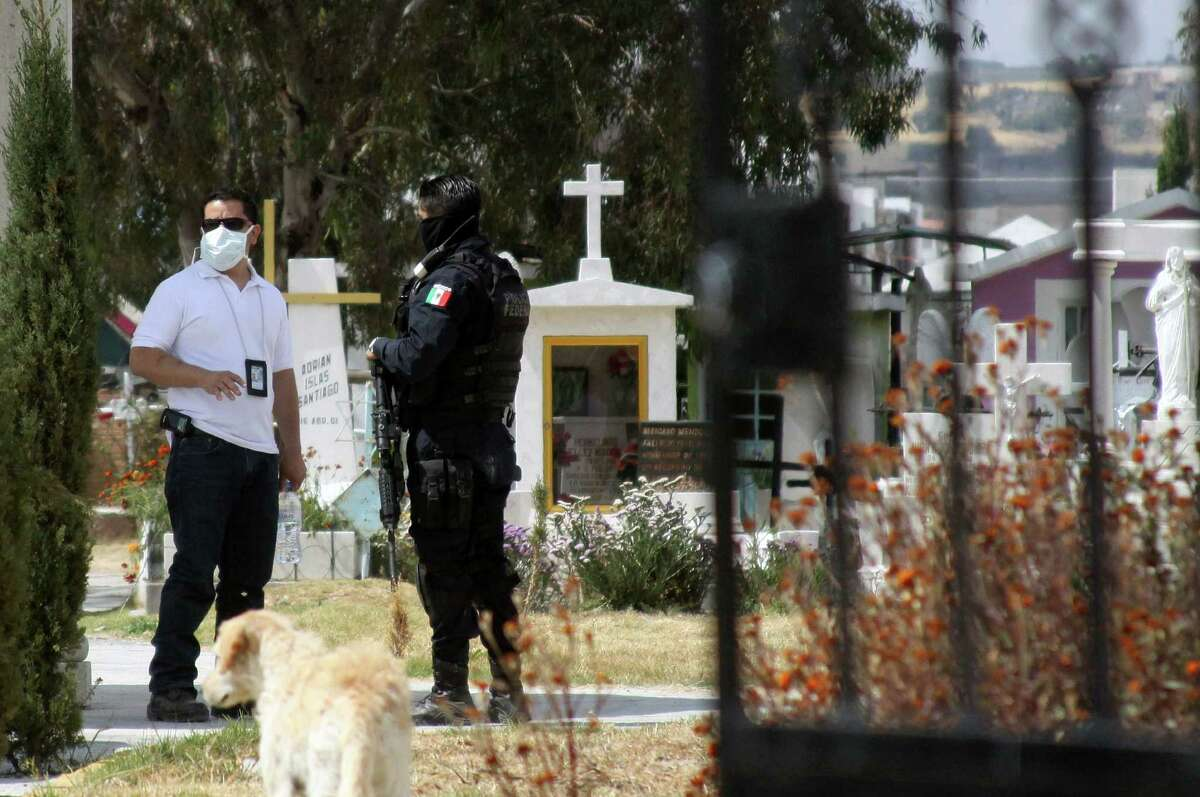 A forensic expert (L) speaks with a federal policeman in a cemetery near Pachuca, Hidalgo State, on October 22, 2012. Mexican experts took DNA samples from the corpse of a relative of the head of Los Zetas, Heriberto Lazcano, aka 'El Lazca', to compare them with those of the Chief of the drug trafficking. Lazcano was reportedly shot dead in Coahuila, one of the border states that have been at the epicenter of Mexico's vicious drug war, believed to have claimed some 60,000 lives since the launch of a military crackdown in 2006. AFP PHOTO/DAVID MARTINEZDavid Martinez/AFP/Getty Images