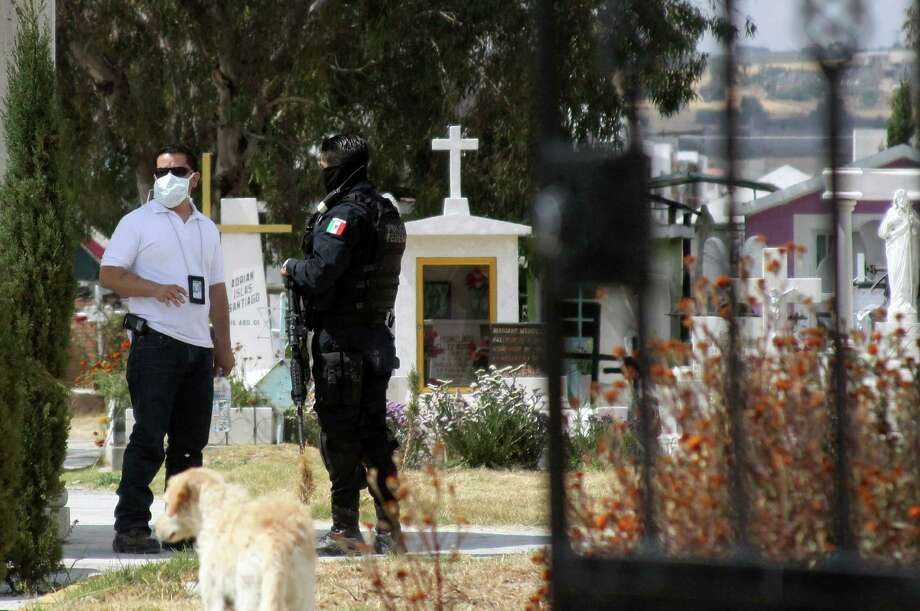A forensic expert (L) speaks with a federal policeman in a cemetery near Pachuca, Hidalgo State, on October 22, 2012. Mexican experts took DNA samples from the corpse of a relative of the head of Los Zetas, Heriberto Lazcano, aka 'El Lazca', to compare them with those of the Chief of the drug trafficking. Lazcano was reportedly shot dead in Coahuila, one of the border states that have been at the epicenter of Mexico's vicious drug war, believed to have claimed some 60,000 lives since the launch of a military crackdown in 2006. AFP PHOTO/DAVID MARTINEZDavid Martinez/AFP/Getty Images Photo: DAVID MARTINEZ, AFP/Getty Images / AFP