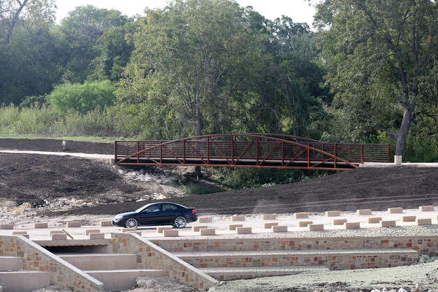 A car crosses the low water crossing just south of Espada Dam along the Mission Reach of the San Antonio River, Monday, Oct. 22, 2012. A part of the reach will open Tuesday with a larger section opening this coming Saturday. As part of the construction, the low water crossing was raised five feet in the process. Photo: Jerry Lara, San Antonio Express-News / © 2012 San Antonio Express-News