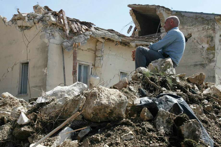 """FILE - In this April 7, 2009 file photo a man sits on rubbles in the village of Onna, a day after a powerful earthquake struck the Abruzzo region in central Italy. An Italian court Monday, Oct. 22, 2012 has convicted seven scientists and experts of manslaughter for failing to adequately warn citizens before an earthquake struck central Italy in 2009, killing more than 300 people. The court in L'Aquila Monday evening handed down the convictions and six-year-prison sentences to the defendants, members of a national """"Great Risks Commission."""" In Italy, convictions aren't definitive until after at least one level of appeals, so it is unlikely any of the defendants would face jail immediately. Scientists worldwide had decried the trial as ridiculous, contending that science has no way to predict quakes. (AP Photo/Alessandra Tarantino, File) Photo: Alessandra Tarantino / AP"""