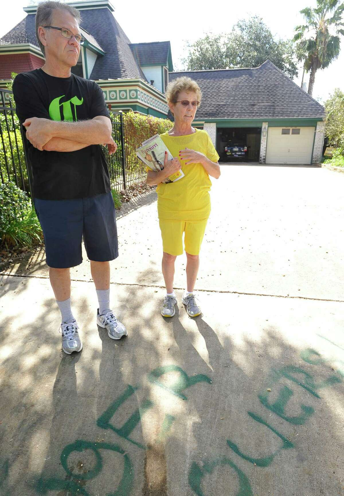 John Stafford, left, and his wife Suzanne discovered racial slurs spray painted on their driveway Saturday morning and one on their Obama/Biden sign that was at the end of the driveway. A Nick Lampson sign had been semi-defaced as well on the opposite side. On Monday morning, they were trying to decide how best to clean off the words that were written in green paint. They believe their political affiliation had something to do with it. Dave Ryan/The Enterprise
