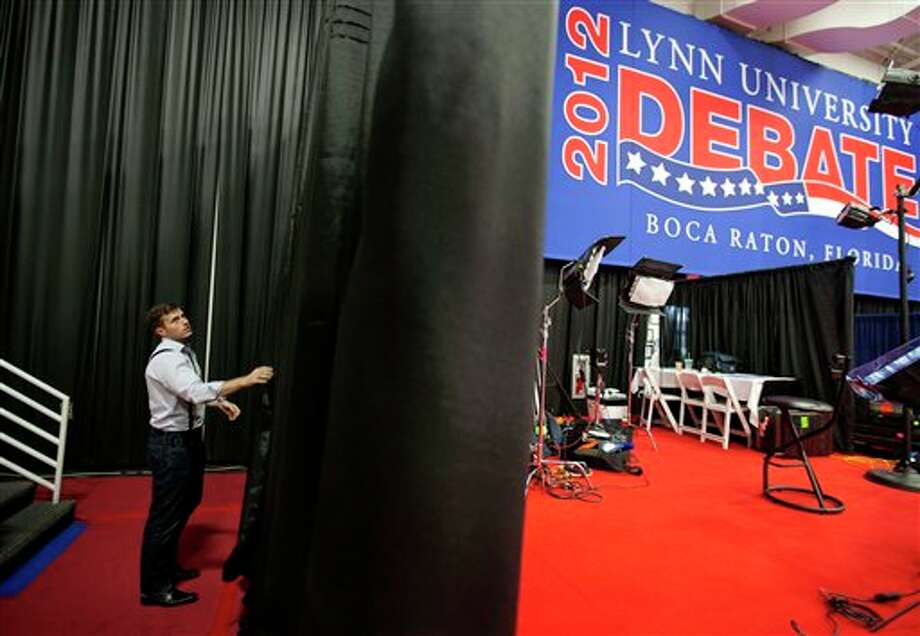A campaign worker works on the set for the spin corner for the President Barack Obama campaign in the media center ahead of Monday's presidential debate between Republican presidential candidate, former Massachusetts Gov. Mitt Romney and Obama, Sunday, Oct. 21, 2012, at Lynn University in Boca Raton, Fla. (AP Photo/David Goldman) Photo: David Goldman, ASSOCIATED PRESS / AP2012