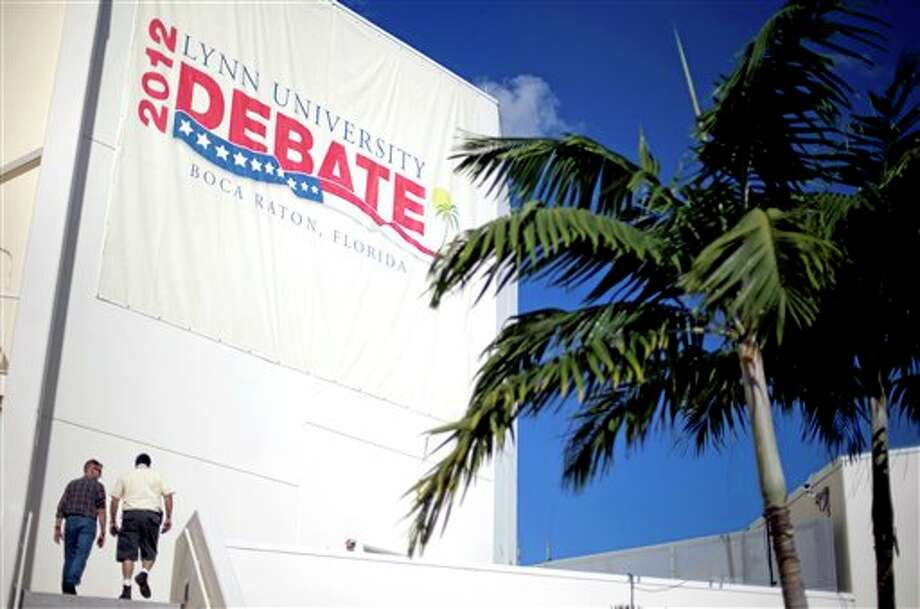 Workers enter the debate hall ahead of Monday's presidential debate between Republican presidential candidate and former Massachusetts Gov. Mitt Romney and President Barack Obama, Sunday, Oct. 21, 2012, at Lynn University in Boca Raton, Fla. (AP Photo/David Goldman) Photo: David Goldman, ASSOCIATED PRESS / AP2012