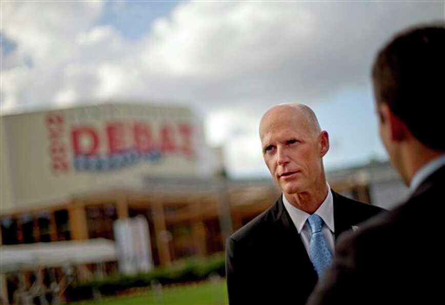 Florida Gov. Rick Scott, left, gives an interview in front of the debate hall ahead of the president