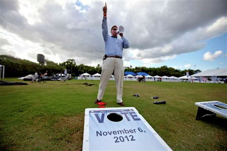 AARP staffer Pete Jeffries yells to entrants of a debate party to take part in a game of bean bag toss ahead of the presidential debate between Republican presidential candidate, former Massachusetts Gov. Mitt Romney and President Barack Obama, at Lynn University  Monday, Oct. 22, 2012, in Boca Raton, Fla. (AP Photo/David Goldman) Photo: David Goldman, AP / AP