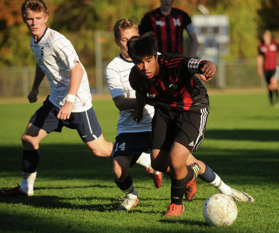 New Canaan's Justin Partierra plays the ball in front of Staples' Jack Scott during their FCIAC soccer matchup at Staples High School in Westport on Monday, October 22, 2012. Photo: Brian A. Pounds / Connecticut Post