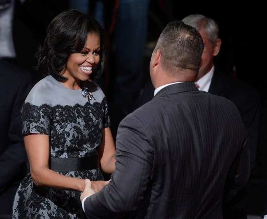 First lady Michelle Obama is greeted before the start of the third presidential debate at Lynn University, Monday, Oct. 22, 2012, in Boca Raton, Fla. (AP Photo/Pool-Michael Reynolds) Photo: Michael Reynolds, AP / EPA Pool