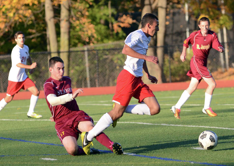 Greenwich's Paul Quiroga (15) avoids a tackle by St. Joe's Tim Keckler (17) during the boys soccer game at Cardinal Stadium in Greenwich on Monday, Oct. 22, 2012. Photo: Amy Mortensen / Connecticut Post Freelance