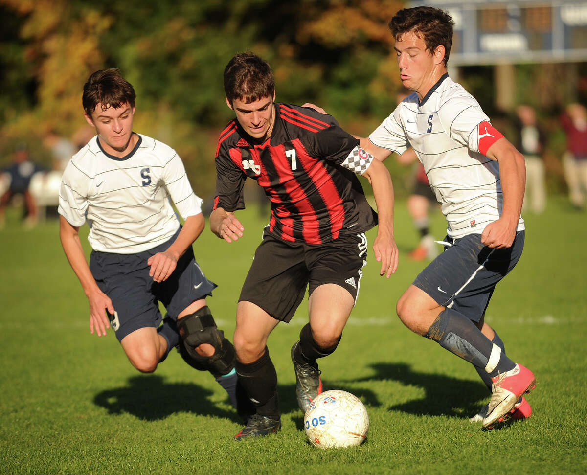 Staples' Jose Alanis, left, and Joseph Greenwald, right, converge on New Canaan's Robert Valente during their boys soccer matchup at Staples High School in Westport on Monday, October 22, 2012.