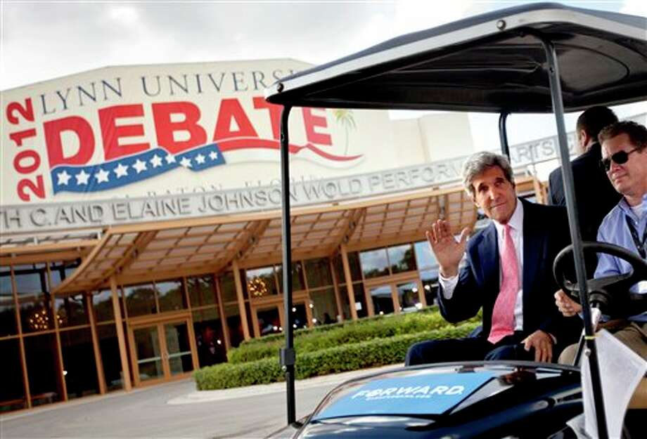 Sen. John Kerry, D-Mass., left, waves as he rides in a golf cart after giving an interview in front of the debate hall ahead of the presidential debate between Republican presidential candidate, former Massachusetts Gov. Mitt Romney and President Barack Obama, at Lynn University  Monday, Oct. 22, 2012, in Boca Raton, Fla. (AP Photo/David Goldman) Photo: David Goldman, AP / AP