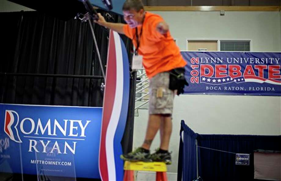 Gaffer Gregg Wolf adjusts set lights on the spin corner in the media center for the Romney campaign ahead of Monday's presidential debate between Republican presidential candidate and former Massachusetts Gov. Mitt Romney and President Barack Obama, Sunday, Oct. 21, 2012, in Boca Raton, Fla. (AP Photo/David Goldman) Photo: David Goldman, ASSOCIATED PRESS / AP2012