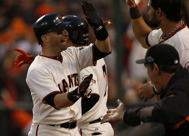 Giants' second baseman Marco Scutaro gets a high five from Angel Pagan after scoring in the 3rd inning during game 7 of the NLCS at AT&T Park on Monday, Oct. 22, 2012 in San Francisco, Calif. Photo: Michael Macor, The Chronicle