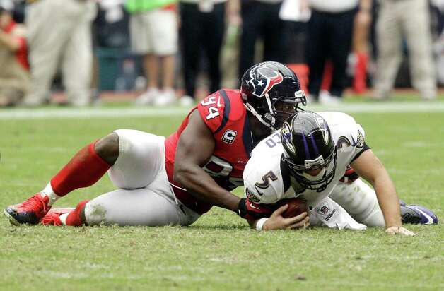 Houston Texans defensive end Antonio Smith (94) sacks Baltimore Ravens quarterback Joe Flacco (5) during the fourth quarter of an NFL football game Sunday, Oct. 21, 2012, in Houston. (AP Photo/Patric Schneider) Photo: Patric Schneider, Associated Press / FR170473 AP