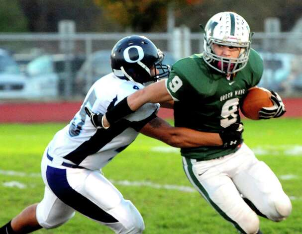 Owen Diaz grabs Ryan Grenier as Oxford plays football at New Milford Monday, Oct. 22, 2012. Photo: Michael Duffy / The News-Times