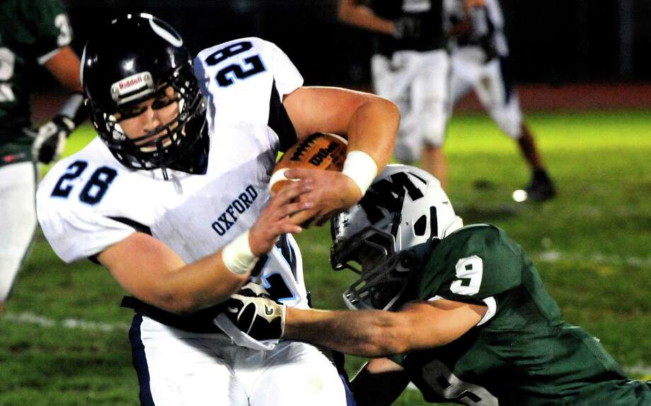 Marcus Esteves carries the ball as Oxford plays football at New Milford Monday, Oct. 22, 2012. Photo: Michael Duffy / The News-Times