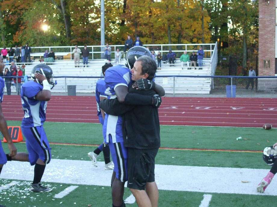 Albany High School Senior Ah-Juan Boyd, left, hugs assistant football coach James Dimideo after the team scored its first victory in four years last weekend. (Courtesy Albany High School)