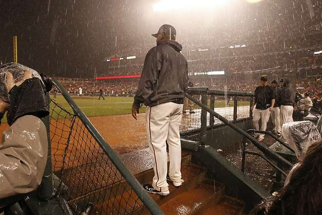 A Giant watches the end of the game as the rain poured down during game 7 of the NLCS at AT&T Park on Monday, Oct. 22, 2012 in San Francisco, Calif. Photo: Michael Macor, The Chronicle