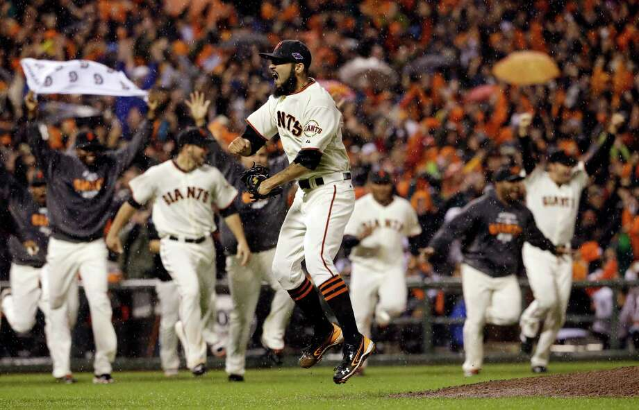 The AT&T Park crowd erupts and the dugout empties after closer Sergio Romo gets the final out to advance the Giants to the World Series, where San Francisco will play the Detroit Tigers for the first time in the postseason. Photo: David J. Phillip / AP