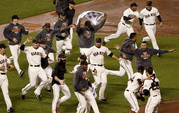 Giants players emerge from the dugout and run to Buster Posey and Sergio Romo (lower right).The San Francisco Giants defeated the St. Louis Cardinals 9-0 to win the National League pennant Monday October 22, 2012 at AT&T park. Photo: Brant Ward, The Chronicle