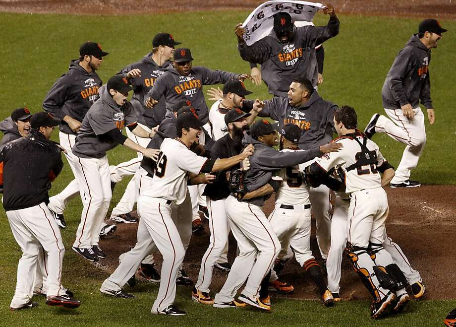 Giant players ran to Buster Posey and Sergio Romo (right) in celebration. The San Francisco Giants defeated the St. Louis Cardinals 9-0 to win the National League pennant Monday October 22, 2012 at AT&T park. Photo: Brant Ward, The Chronicle
