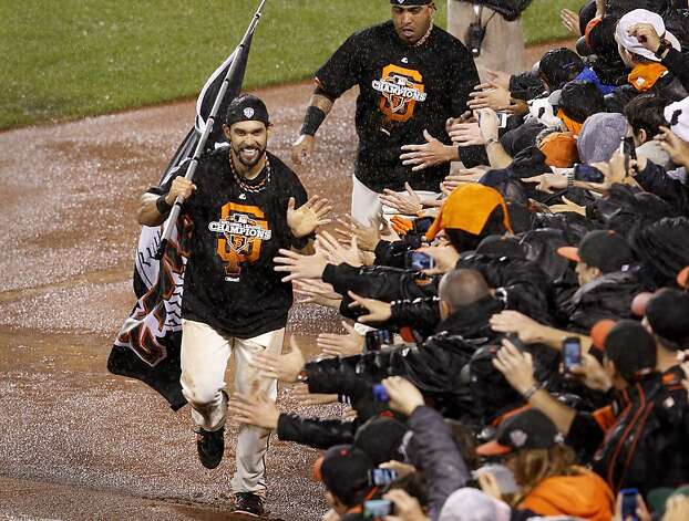 Angel Pagan (left) runs along the right field wall, celebrating with fans after the shutout of the Cardinals. Photo: Brant Ward, The Chronicle