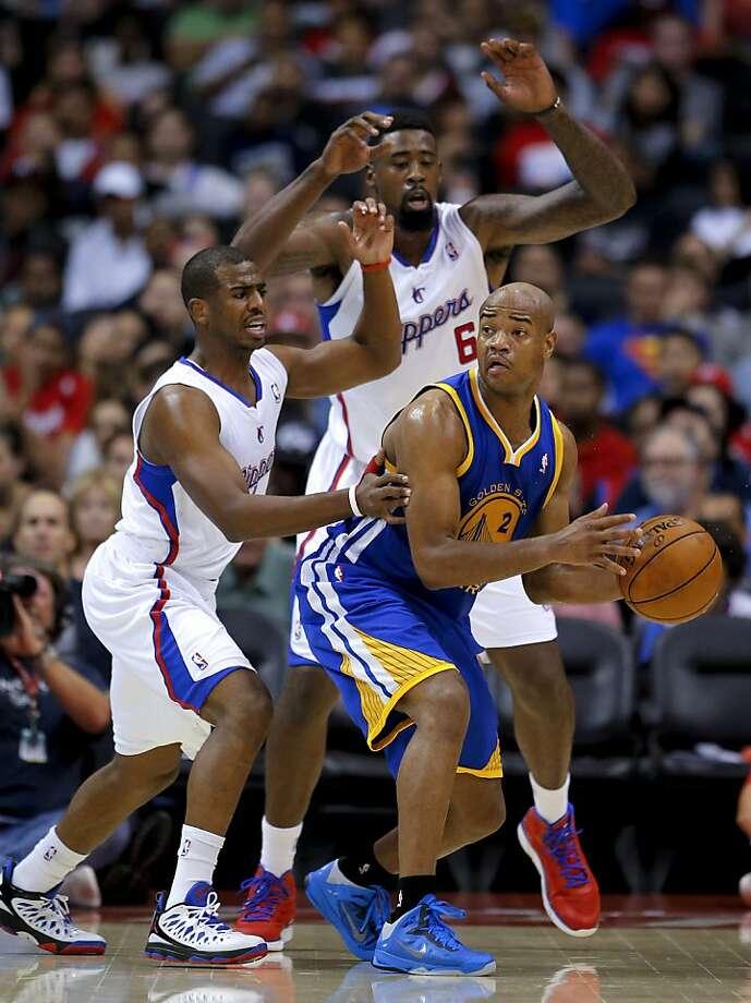 The Warriors' Jarrett Jack faces a double team from Chris Paul (left) and DeAndre Jordan. Photo: Jae Hong, Associated Press