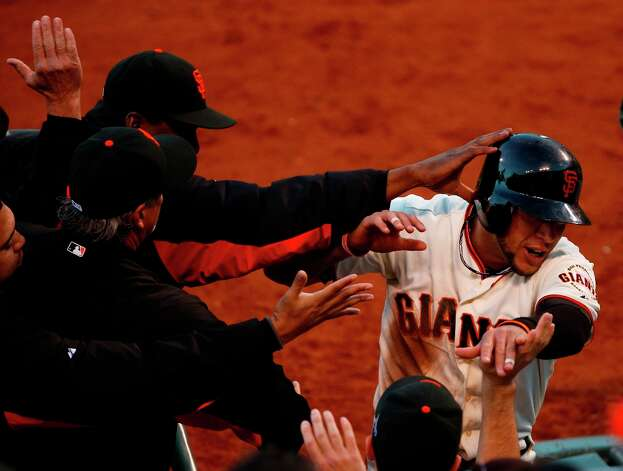 Giants' left fielder Gregor Blanco is greeted in the dugout after scoring in the 3rd inning during game 7 of the NLCS at AT&T Park on Monday, Oct. 22, 2012 in San Francisco, Calif. Photo: Beck Diefenbach, The Chronicle / ONLINE_YES