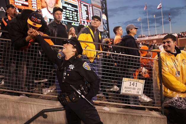 SFPD Officer Michelle Alvis receives a kiss on the hand from Giants fan Eddie Nazlou, of Santa Clara, after she gave him a high five, at right, James Adams, from Landmark Security, looks on during Game 7 of the NLCS between the San Francisco Giants and the St. Louis Cardinals at AT&T Park Monday, October 22, 2012 in San Francisco, Calif. Photo: Pete Kiehart, The Chronicle