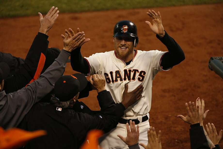 Hunter Pence is greeted after scoring in the third, the same inning in which his odd, thrice-hit double was the key play. Photo: Beck Diefenbach, The Chronicle