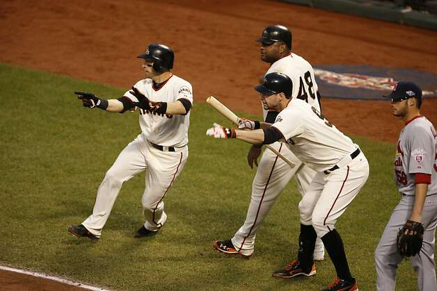 Giants' second baseman Marco Scutaro , Pablo Sandoval, and Brandon Belt watch as Buster Posey scores in the 3rd inning during game 7 of the NLCS at AT&T Park on Monday, Oct. 22, 2012 in San Francisco, Calif. Photo: Beck Diefenbach, The Chronicle