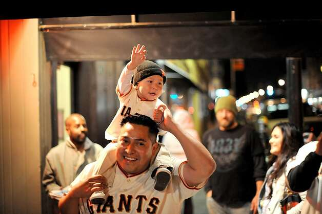Wearing matching Buster Posey outfits, Enrique Escalante and his son Gabriel Escalante, 16  months, celebrate in the Mission as their team beats the Cardinals on Monday, Oct. 22, 2012, in San Francisco. Photo: Noah Berger, Special To The Chronicle