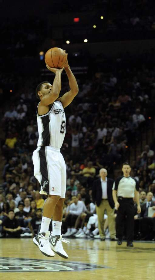 Patty Mills of the Spurs hits a long-range 3-point shot to end the third quarter as the Spurs defeat the Phoenix Suns, 105-91, during NBA action at the AT&T Center on Saturday, April 14, 2012. Photo: BILLY CALZADA, San Antonio Express-News / SAN ANTONIO EXPRESS-NEWS