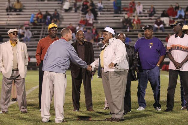 Jasper Coach Darrell Barbay shakes the hand of Clifton WIlliams during a halftime ceremony honoring the members of the 1968 Rowe Tigers championship football team. Photo: Jason Dunn