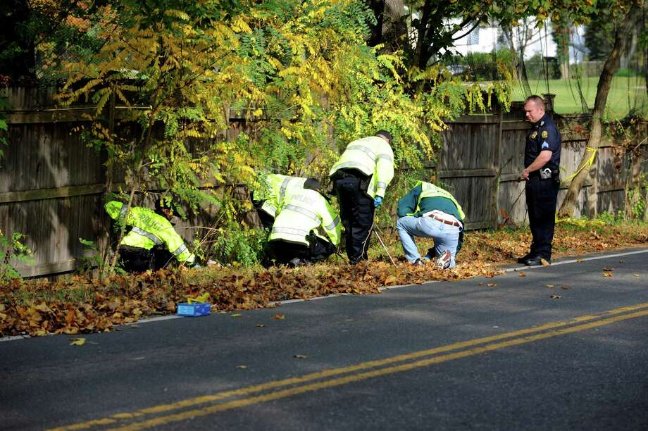 Police investigators search along Indian Field Road in Cos Cob Tuesday, Oct. 23, 2012, following a shooting at the location the night before. Shots were fired at two passengers in a car, in what police are saying was not a random shooting. No one was injured. Photo: Helen Neafsey / Greenwich Time