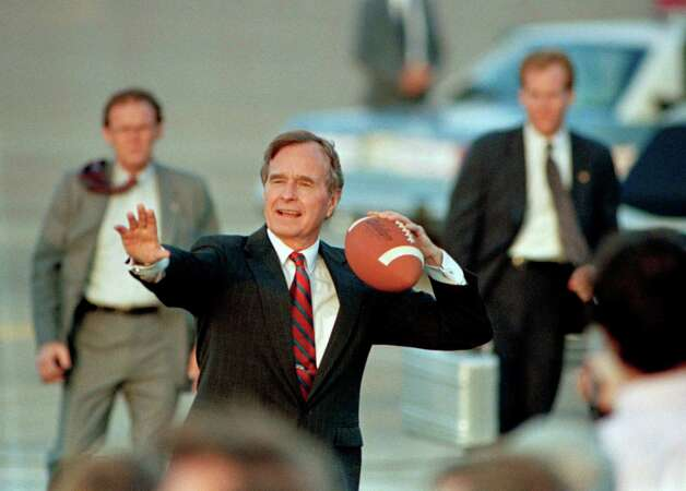 Vice President George Bush tosses a football back to members of the traveling press corps after arriving in Houston on Monday, Nov. 7, 1988.   Bush, in the last full day of campaigning, returned to Houston where he will vote on Tuesday. (AP Photo/Eric Gay) Photo: Eric Gay, ASSOCIATED PRESS / AP