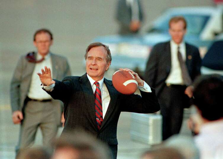 Vice President George Bush tosses a football back to members of the traveling press corps after arri