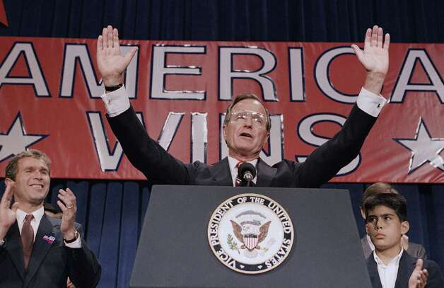 In this Nov. 9, 1988, President-elect George H. W. Bush holds his hands up to acknowledge the crowds applause, and ask them to allow him to continue his speech during his victory rally with grandson, George P. Bush, right, and son, George W. Bush, left, in Houston, Texas. Bush trounced Michael Dukakis 426-111 in the electoral vote, but the popular vote was closer, 53 percent to 46 percent. Photo: AP / AP