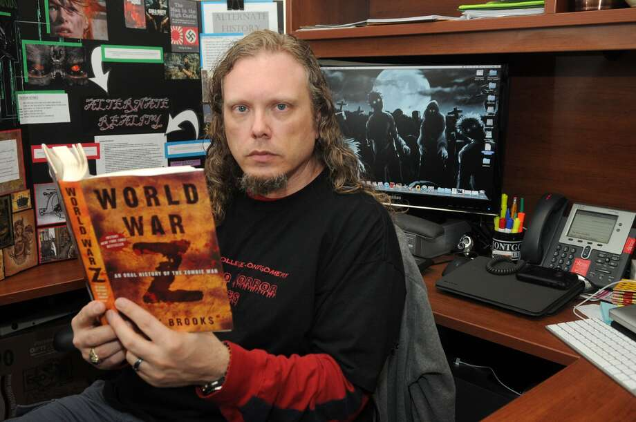 Jared Cootz, the professor of sociology at Lone Star College-Montgomery, shows off one of his textbooks in his office. Cootz offers a different twist on readings in his class. Photo: Jerry Baker
