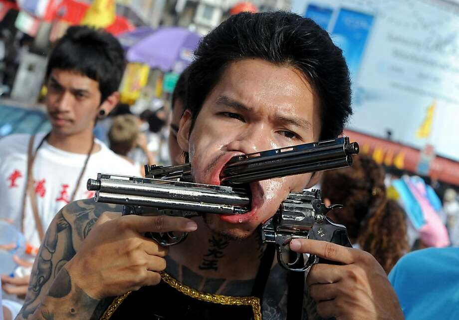 Shooting from the lip:A devotee of the Chinese Jui Tui Shrine  marches in a street procession marking the Vegetarian Festival in  Phuket, Thailand. Worshippers slash themselves with swords, pierce their  cheeks and commit other painful acts to purify themselves while  assuming the sins of the community. Photo: Pornchai Kittiwongsakul, AFP/Getty Images