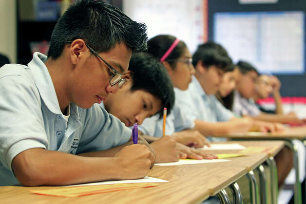 Seventh grader Daniel Garcia joins a rown of students concentrating on their assignment in reading class as KIPP Camino Academy conducts classes  on October 17, 2012. Photo: Tom Reel, San Antonio Express-News / ©2012 San Antono Express-News