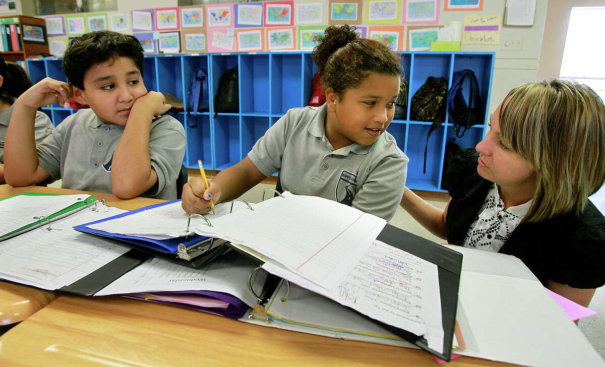 Fifth grade history teacher Lisha Loveberry helps Roman Gonzales and Sol Escobedo with an exercise as KIPP Camino Academy conducts classes on October 17, 2012.