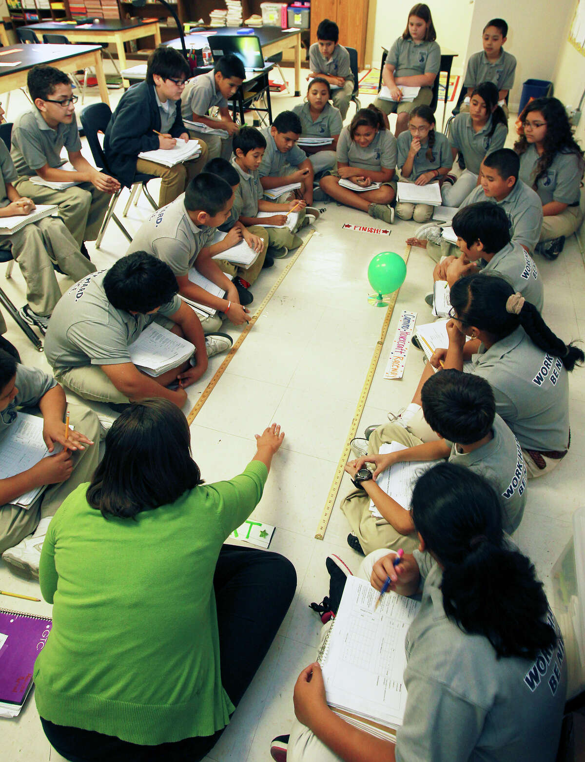 Students in Jennifer Ortegon's fifth grade science class time the release of air from a baloon experiment as KIPP Camino Academy conducts classes on October 17, 2012.