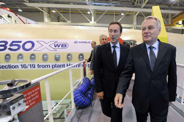 French Prime Minister Jean-Marc Ayrault, right, and Airbus President and Chief Executive Officer Fabrice Bregier leave after visiting  an Airbus A350 XWB on the final assembly line in Toulouse, France, Tuesday Oct. 23, 2012. Photo: AP