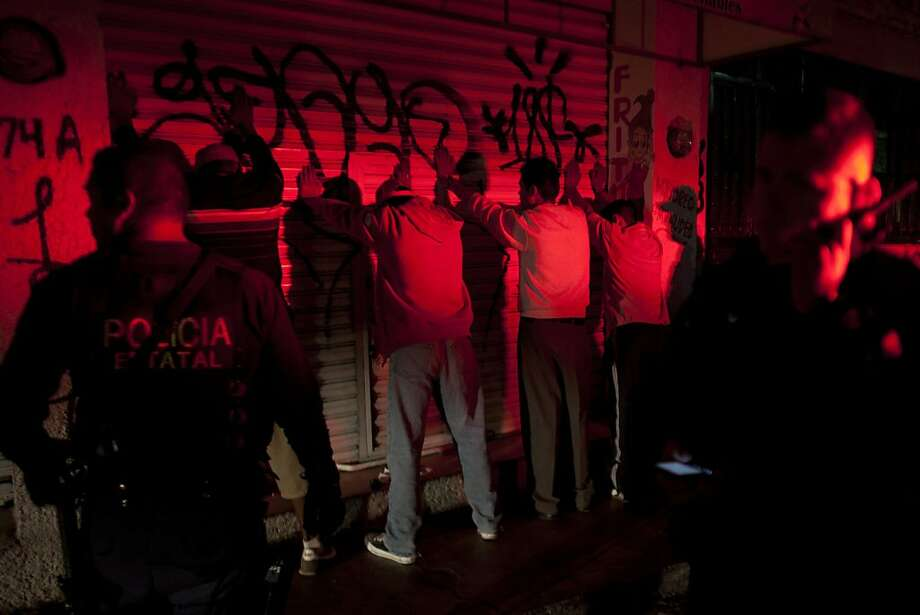 Police on routine patrol in Morelia line up a group of men along a wall and prepare to search them. Photo: Alexandre Meneghini, Associated Press