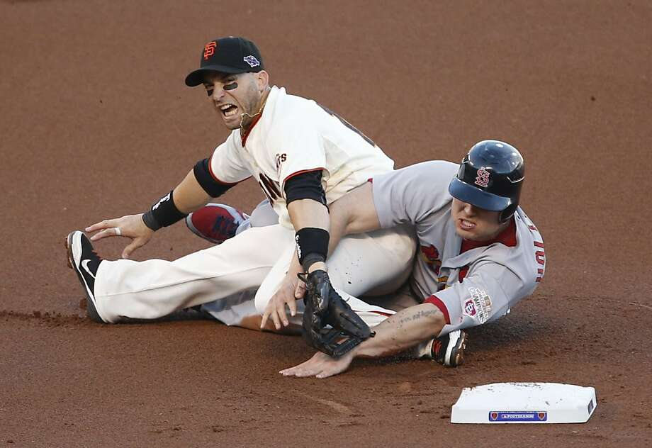 Giants' third baseman Marco Scutaro grimaces after Cardinals' left fielder Matt Holliday slides into him on a fielder's choice out in the first inning during game 2 of the NLCS on Monday, Oct. 15, 2012 at AT&T Park in San Francisco, Calif. Photo: Beck Diefenbach, Special To The Chronicle